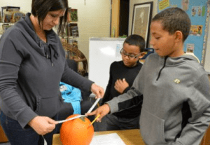 Holly Grays measures pumpkins with her sons, Taeron and Donate.