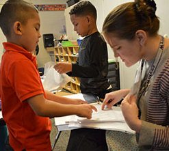 First-grader Gustavo Aburto Ambriz shows his story to EL teacher Nicole Adams.