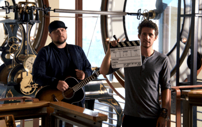 Compass College Senior, Jonathan Clark (right), holds the film slate as Micah Tyler (right) prepares for the next take. (Photo courtesy of Compass College of Cinematic Arts.)