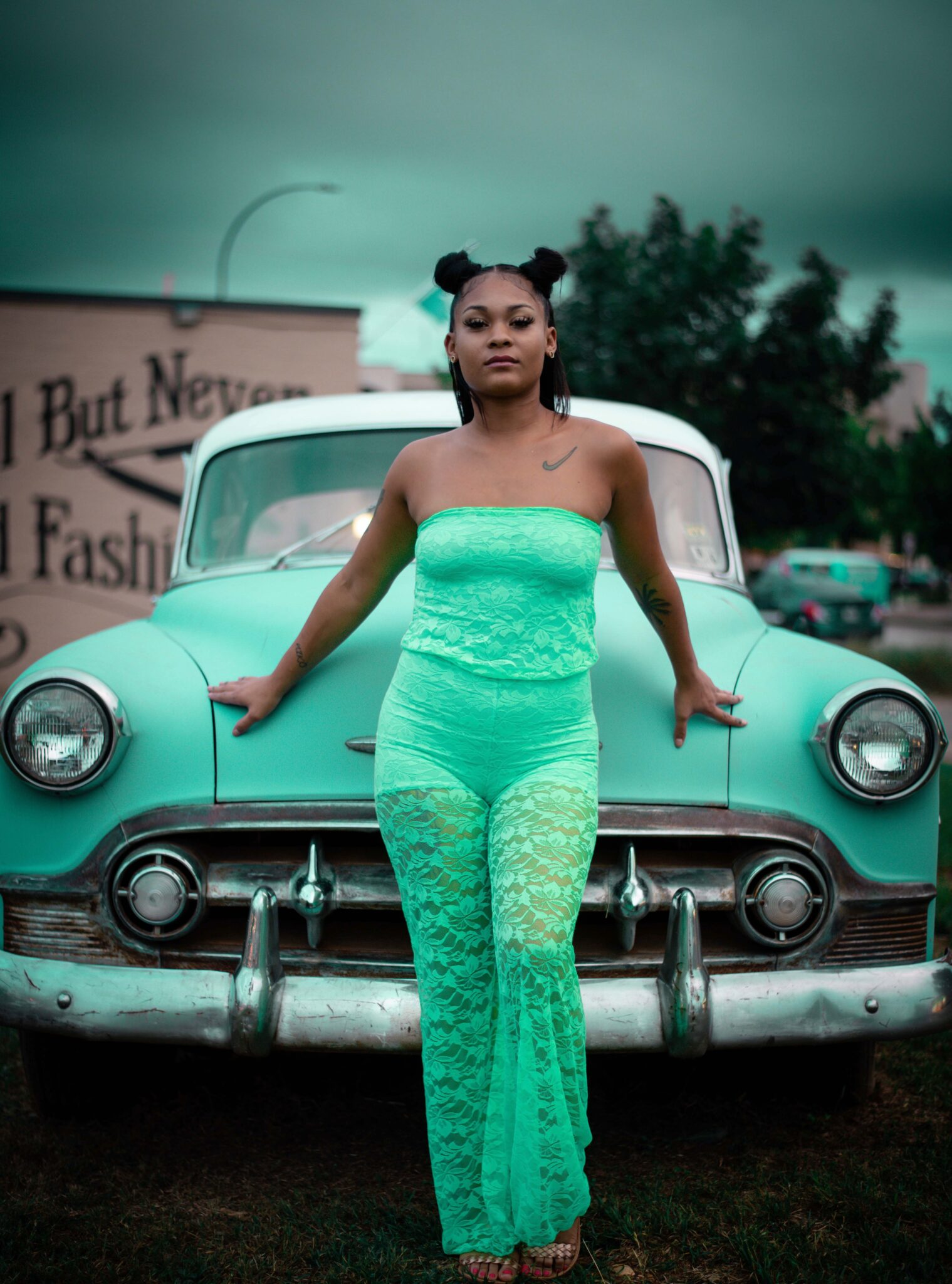 woman leaning on teal car