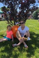 Isla Cross and Debbie Morin sit in the shade to cool off at the 2018 Family Fair.