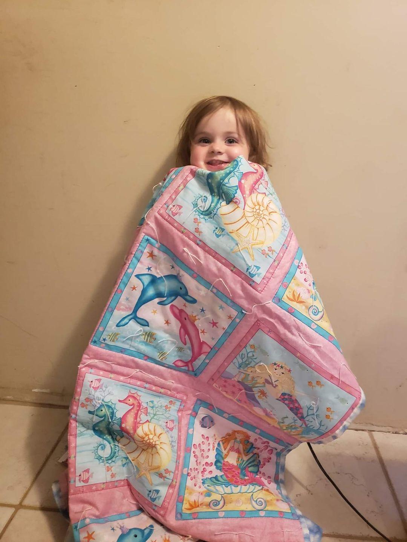 girl holding pink blanket