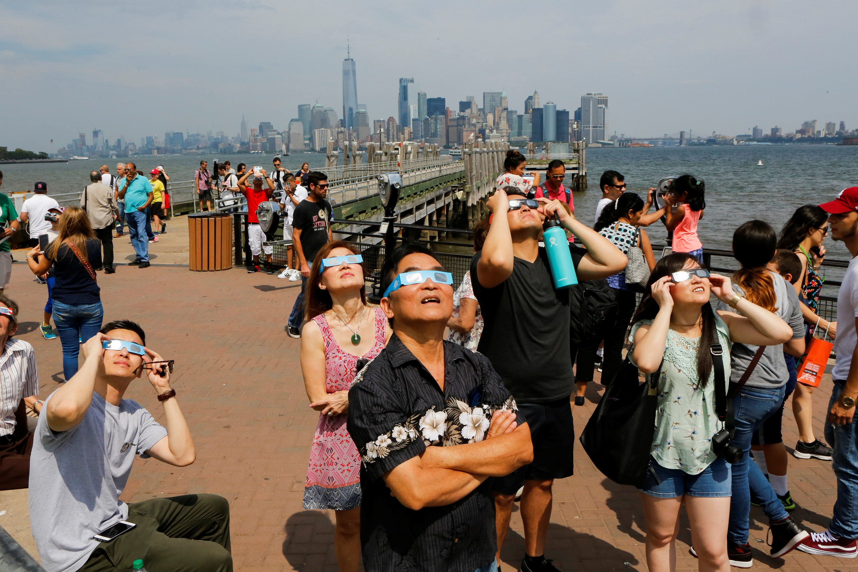 People view the solar eclipse at Liberty State Island as the Lower Manhattan and One World Trade center are seen in the background in New York, U.S., August 21, 2017. Location coordinates for this image are 40.4124' N, 74.237'. W