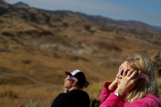 Enthusiasts watch a solar eclipse before it's totality from atop Carroll Rim Trail at Painted Hills, a unit of the John Day Fossil Beds National Monument, near Mitchell, Oregon, U.S. August 21, 2017. Location coordinates for this image is near 44º39'117'' N 120º6'042'' W. REUTERS/Adrees Latif