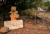 A sign left by an evacuated resident, fleeing wildfires in the heart of the California's wine country, rests against a fire hydrant in the evacuated town of Calistoga, California, U.S., October 12, 2017. REUTERS/Noel Randewich