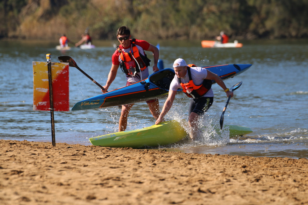 Two male paddlers jostling for position as they exit and pick up boats at the start of a sand portage