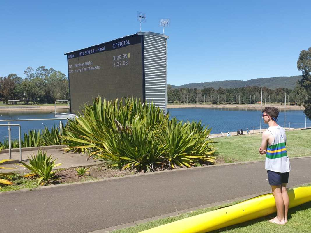 View of results board at Sydney International Regatta Centre, with paddler and boat in the foreground.
