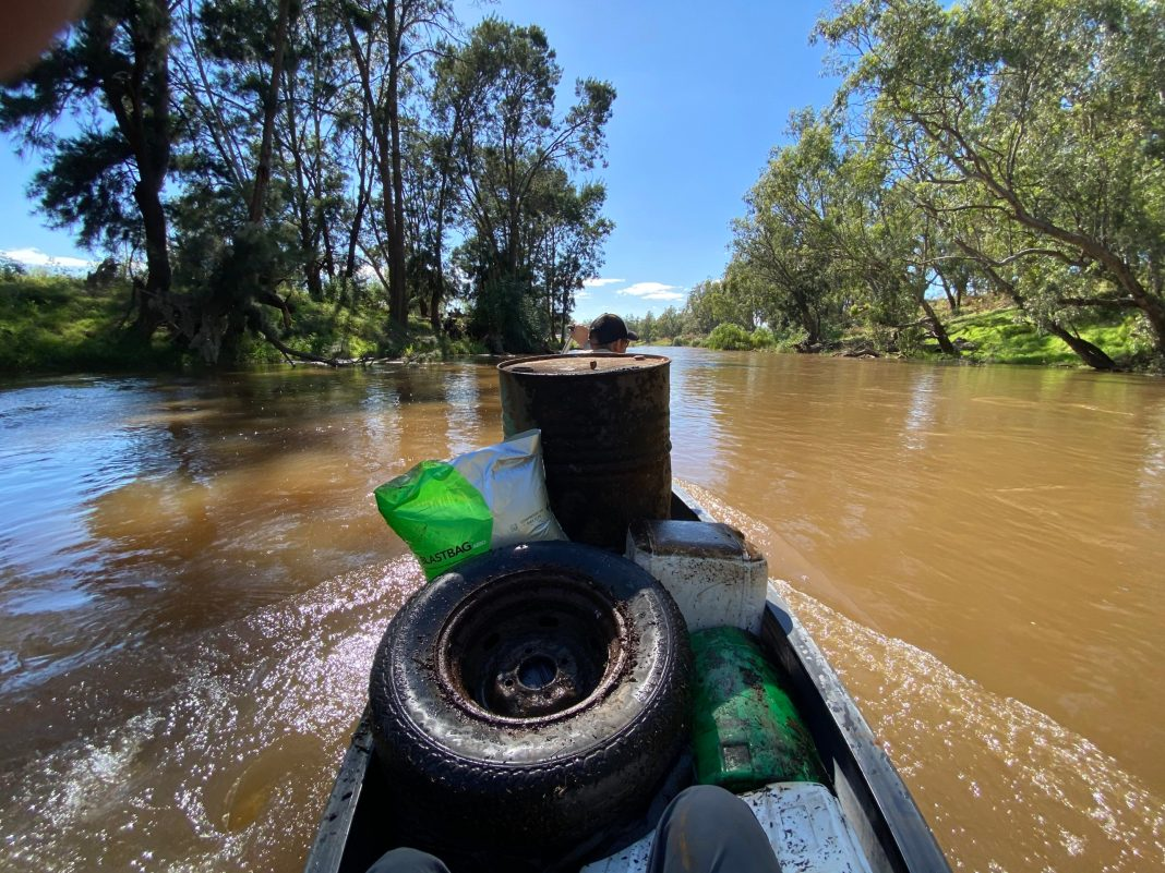 View from canoe in the middle of a river, packed with a tyre, drum and other garbage found in the river.
