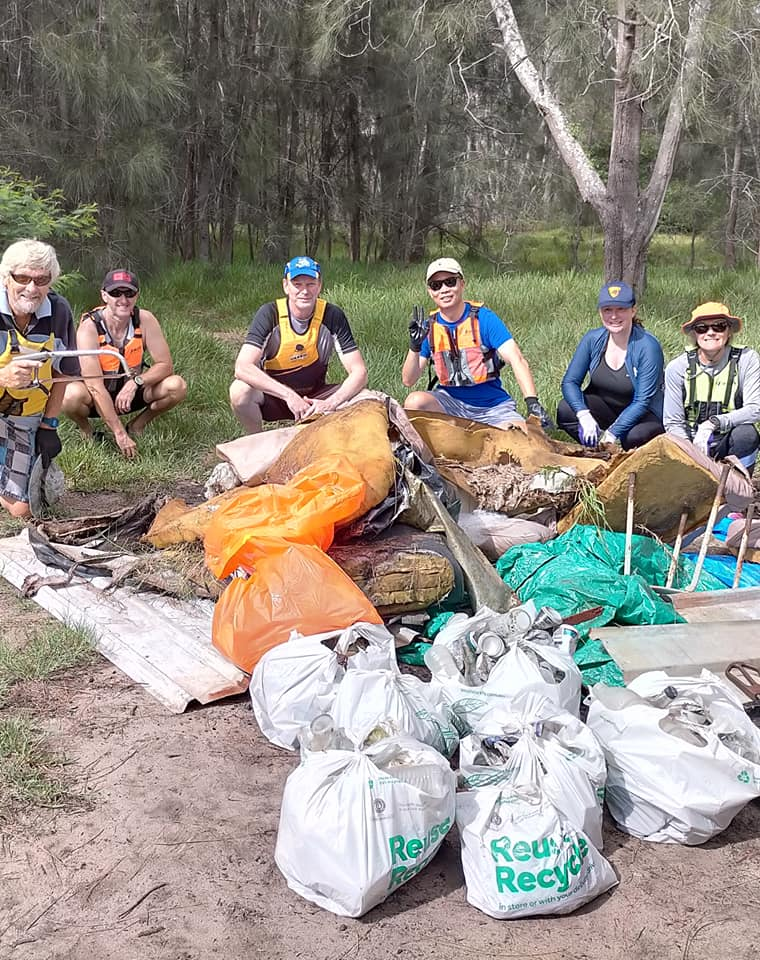 Paddlers in lifejackets crouched around bags of rubbish collected from local river
