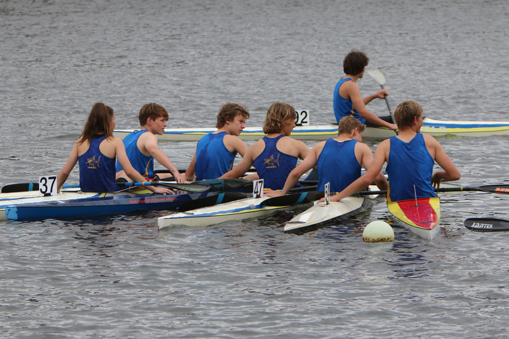 Group of teenage paddlers in blue singlets rafted up in boats and facing away from camera.