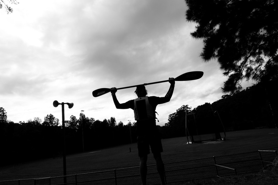Black and white image looking up to paddler stretch with paddle above head