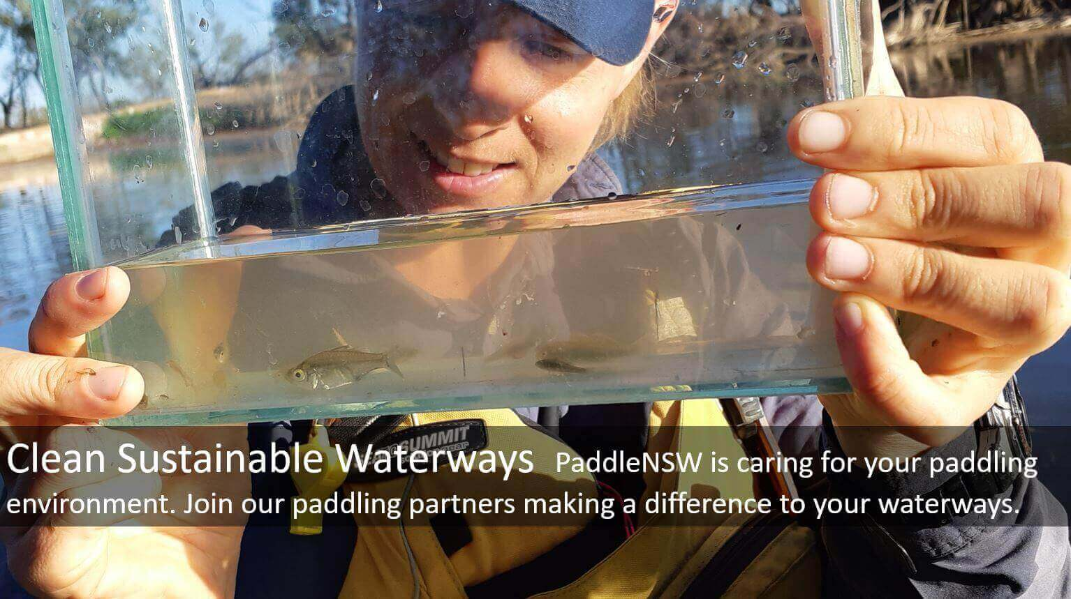 Paddler holding up and examining fish in clear tank, with text on Clean Sustainable Waterways
