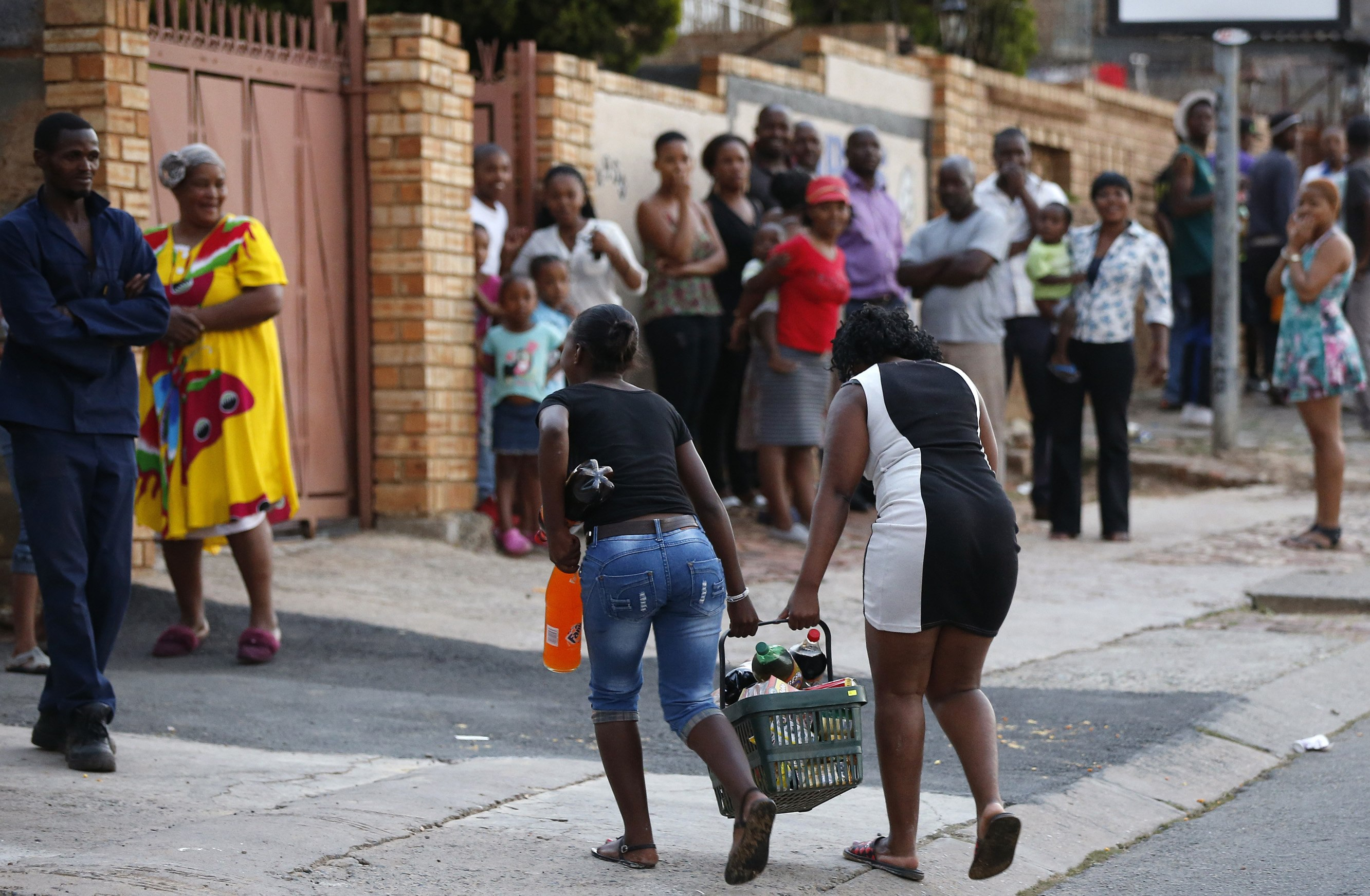 Locals look on as young women run with items from a shop believed to be owned by a foreigner, in Soweto