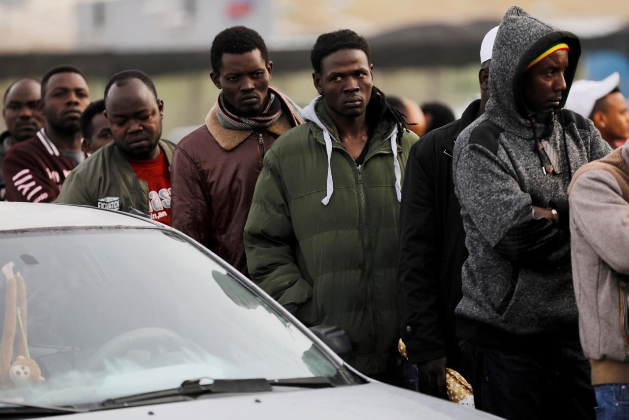 FILE PHOTO: African migrants wait in line for the opening of the Population and Immigration Authority office in Bnei Brak