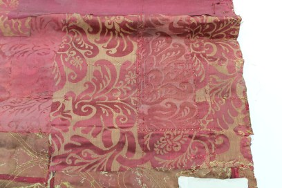 Pink damask patch at bottom of curtain on Spangled bed, patched with another patch of same damask ©National Trust/Textile Conservation Studio.