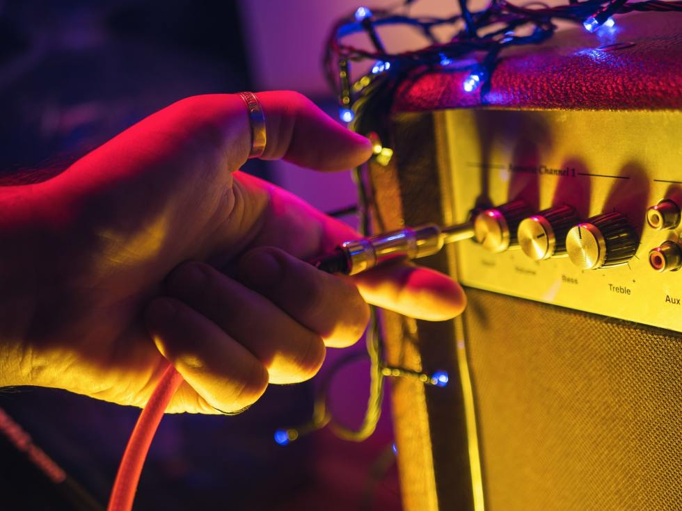 Mans hand plug in jack to guitar amplifier