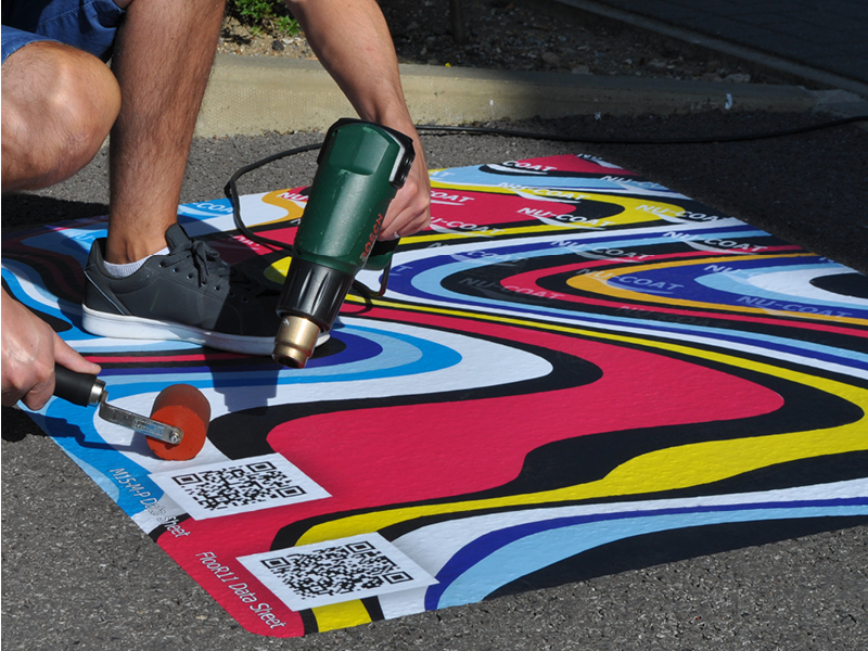 MaxGRAB base print vinyl with a brighly coloured wavey graphic and FlooR11 slip rated floor graphic laminate being installed with a heat gun and soft roller outside onto tarmac.