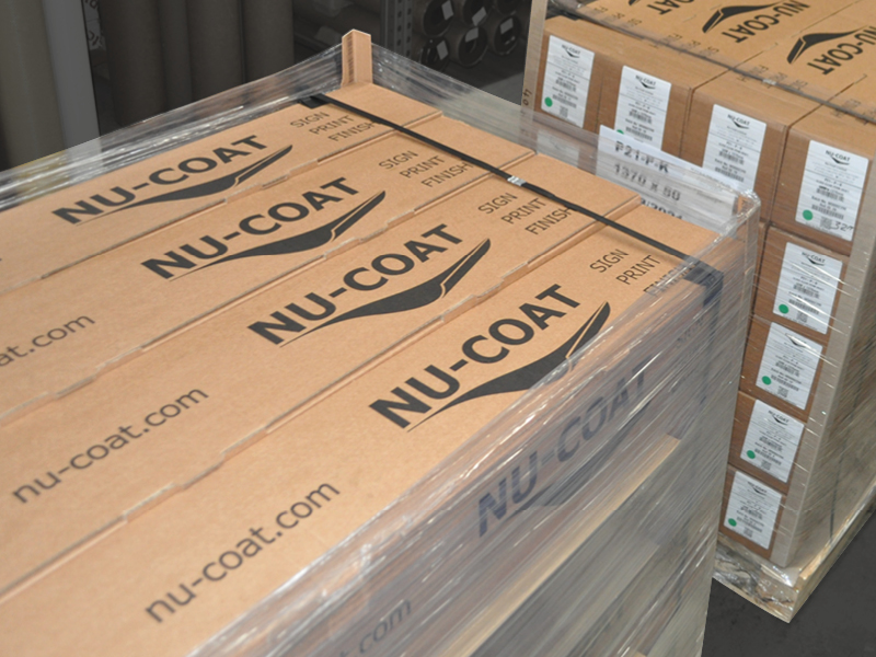 Nu-Coat branded brown box eco-packaging neatly stacked on a pallet in the warehouse with corner protectors and cling film for added protection of the media rolls.