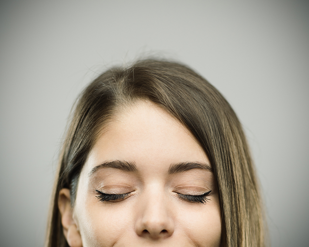 Close-up portrait of confident beautiful young woman with resting expression. Real people female is against gray background with closed eyes and happy face. She has long brown hair. Horizontal studio photography from a DSLR camera. Sharp focus on eyes.