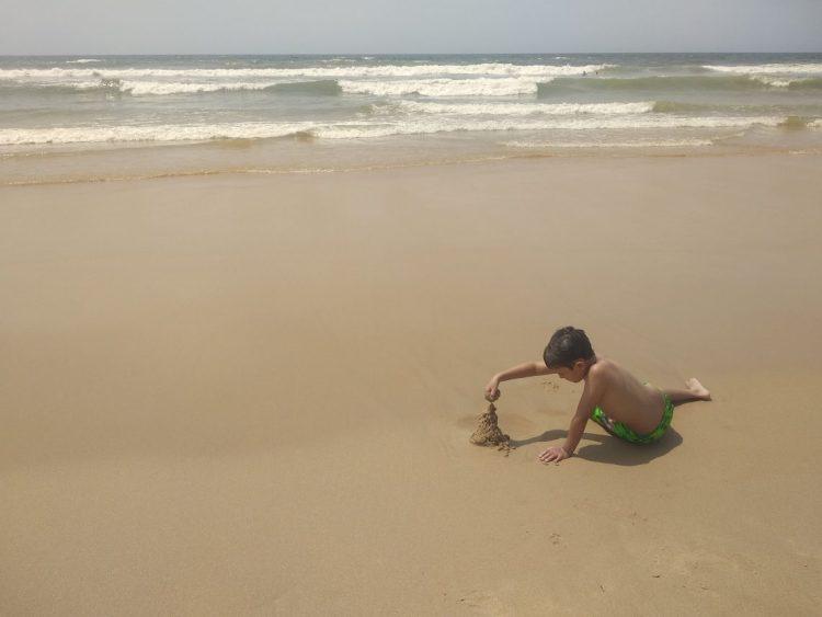 niño en la playa jugando con arena