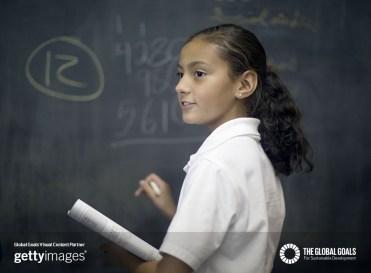 Fifth grade girl at chalk board.