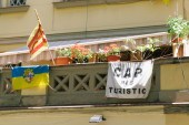 From left to right: A Barceloneta neighborhood flag, a Estelada flag and an anti-tourism flag all hang off a balcony in the Barceloneta neighborhood.