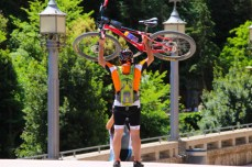 A biker holds his bike above his head for a picture. The picture is in celebration of his completion of a race up the Montserrat mountains. Photo by Clara Cutbill.