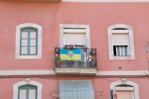 A Barceloneta neighborhood flag hangs off a balcony in Barceloneta.