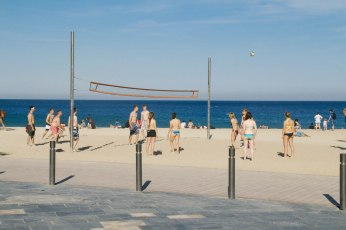 A group of people play volleyball on the beach in Barceloneta. The beach is covered with nets and many games like this one can be seen along the entire beach. Photo by Clara Cutbill.