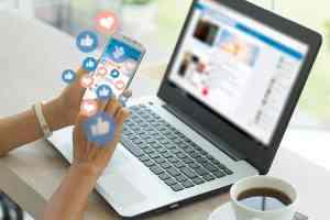 Inimene töötab nutitelefoni ja sülearvutiga