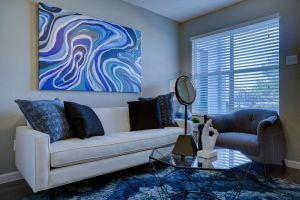 A living room of a fully furbished apartment, in blue and white.
