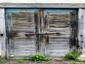 Shabby wooden doors locked with a metal bar.