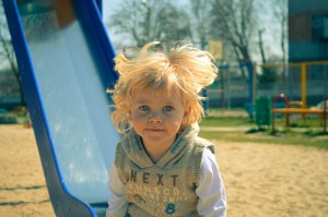 A blonde, blue-eyed boy in a cute hoodie sitting at the bottom of a slide on a playground. His hair is ruffled from the wind and he looks very happy.