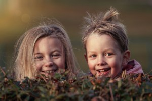 Two children in nature, laughing happily. They live in family neighborhoods in Hamilton, and are having a lot of fun.