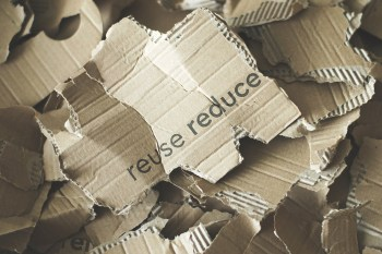 Torn cardboard with 'reduce' and 'reuse' written on it