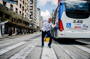A lad performing a dance move in front of a bus