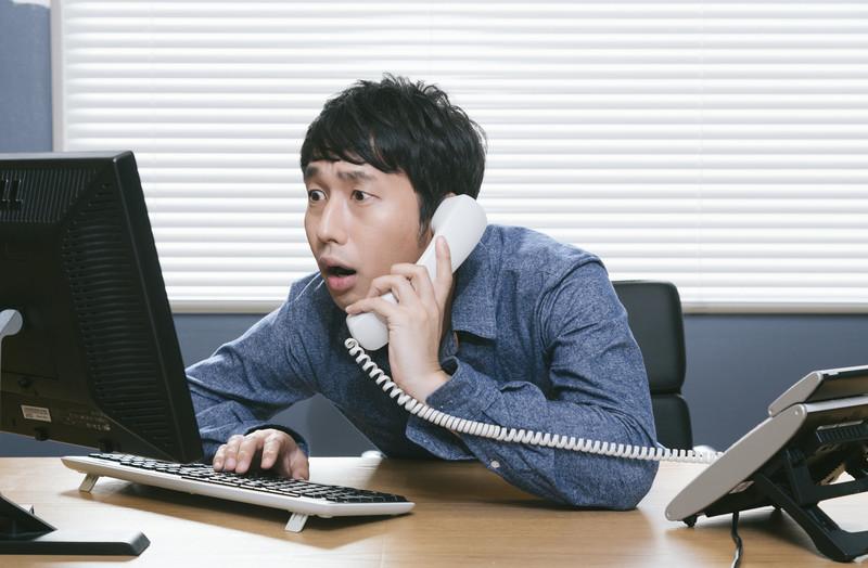 電話をしながらパソコンを見る男性