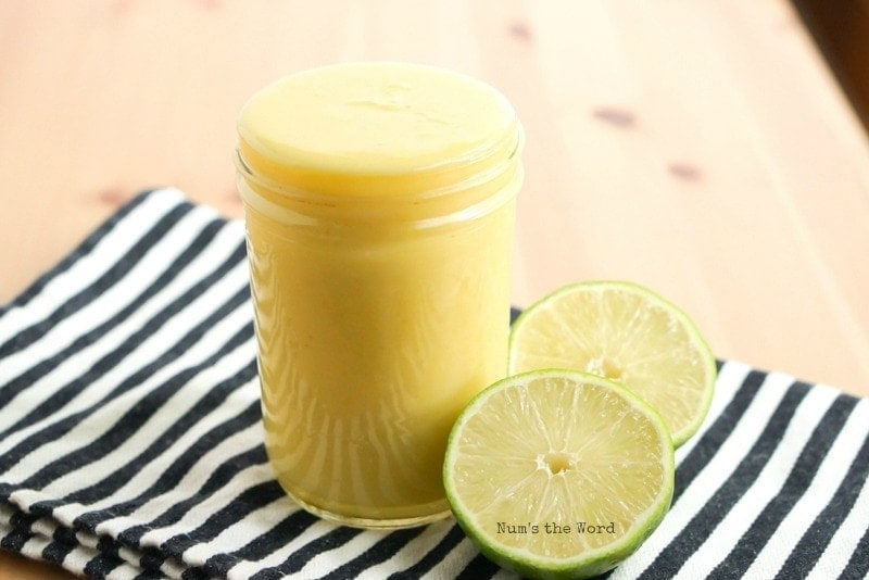 Homemade Lime Curd - side view of lime curd in glass jar with sliced limes next to it.