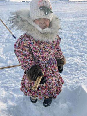1510Alexandra Klengenberg_st.jpg<br /> Alexandra Klengenberg<br /> Kugluktuk<br /> 4-year-old Kyla Anablak fishing on 4 Mile Bay. Her parka was made last spring with Wolf Fur as a sunburst to keep warm on cold winter days.