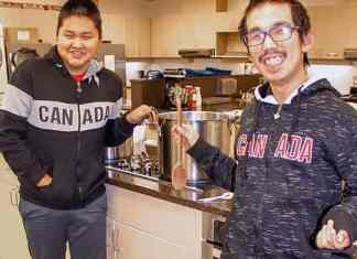 Grade 10 students Anthonese Mablik, left, and Shane Mapsalak are all smiles as they prepare to serve some hot caribou stew for students in grades seven to 12 at Tuugaalik High School in Naujaat on Jan. 10, 2019. Photo courtesy Julia MacPherson