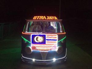 """Laura conduciendo y David de copiloto. De frente furgoneta hippy con bandera malaya iluminada en el capó y letras luminosas en el techo que pone """"putrajaya"""""""