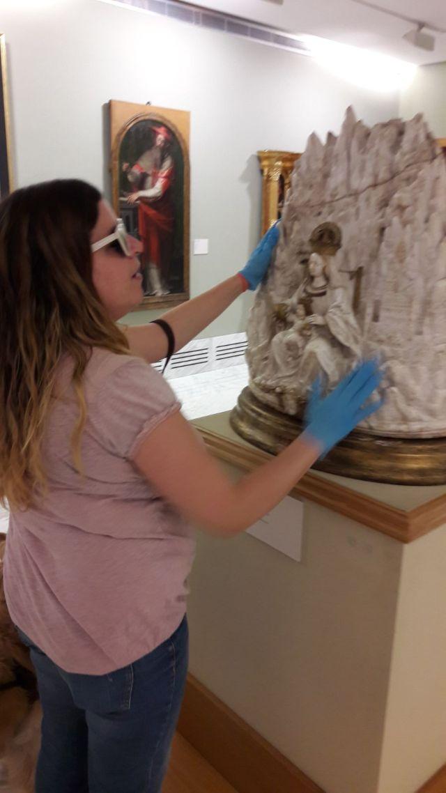 Laura tocando una escultura de la montaña de Montserrat con la virgen es su base