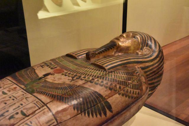 Sarcófago de faraón. Se ve la parte superior, en tonos cobrizos, con unas grandes alas en el pecho y la típica barba rizada de faraón