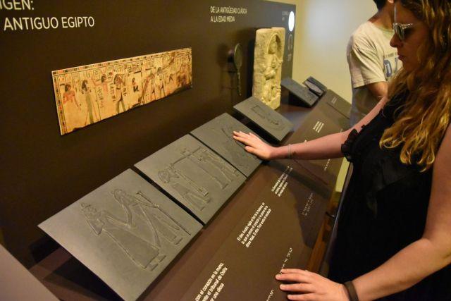 Laura tocando recreaciones de los papiros en relieve