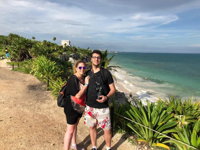 Laura y David en un camino de Tulúm. Es el borde de una montaña. Detrás suya se ven a la izquierda una ruinas mayas, a la derecha el mar con sus olas y entre medias la selva.