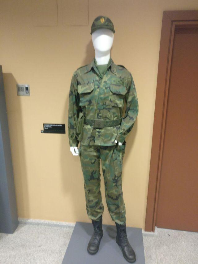 Uniforme del ejército español en un maniquí con chaqueta pantalones y gorra, en tonos verdes.