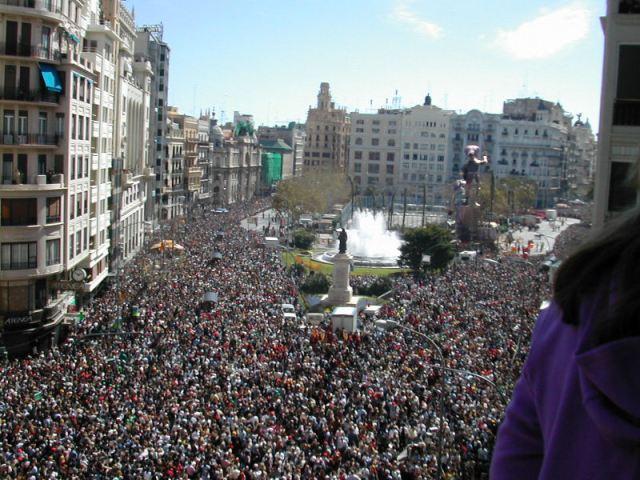 La plaza dell ayuntamiento de valencia desde un balcón. Una tupida manta de personas y al final el humo de la mascletá.