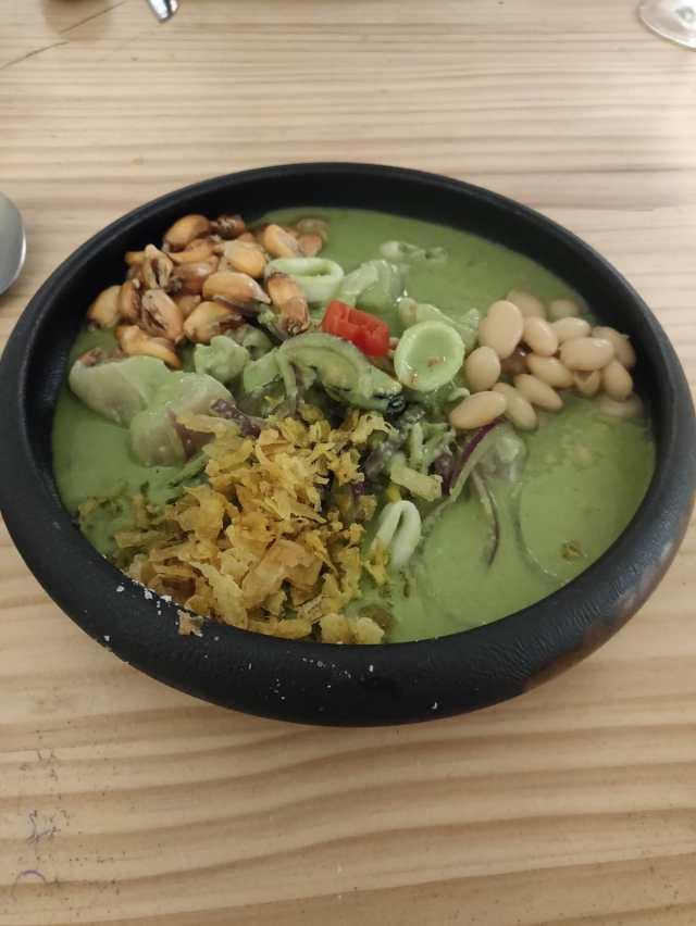 Ceviche verde sobre un cuenco parecido al plato de antes. se ve el fondo verde y por la salsa verde y encima todos los ingredientes