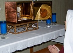 A Handmaid adores the Lord in a private oratory.