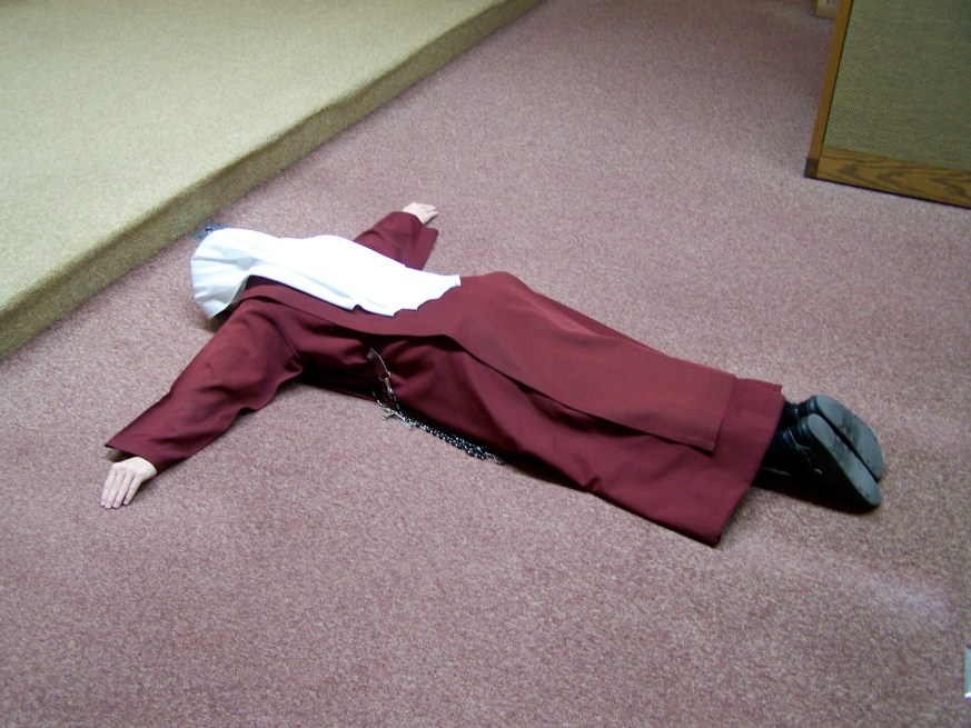 Lying prostrate before the altar during the Litany of the Saints.